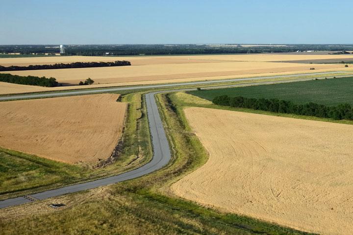 a road winds between golden fields of wheat in Kansas